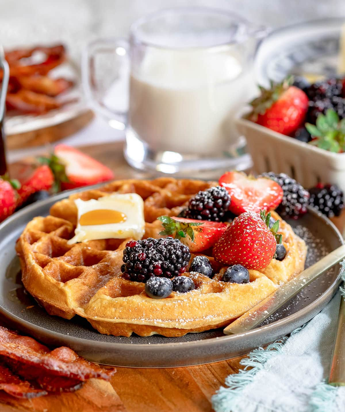 one waffle topped with berries and powdered sugar as well as some butter and syrup. milk and bacon in background.