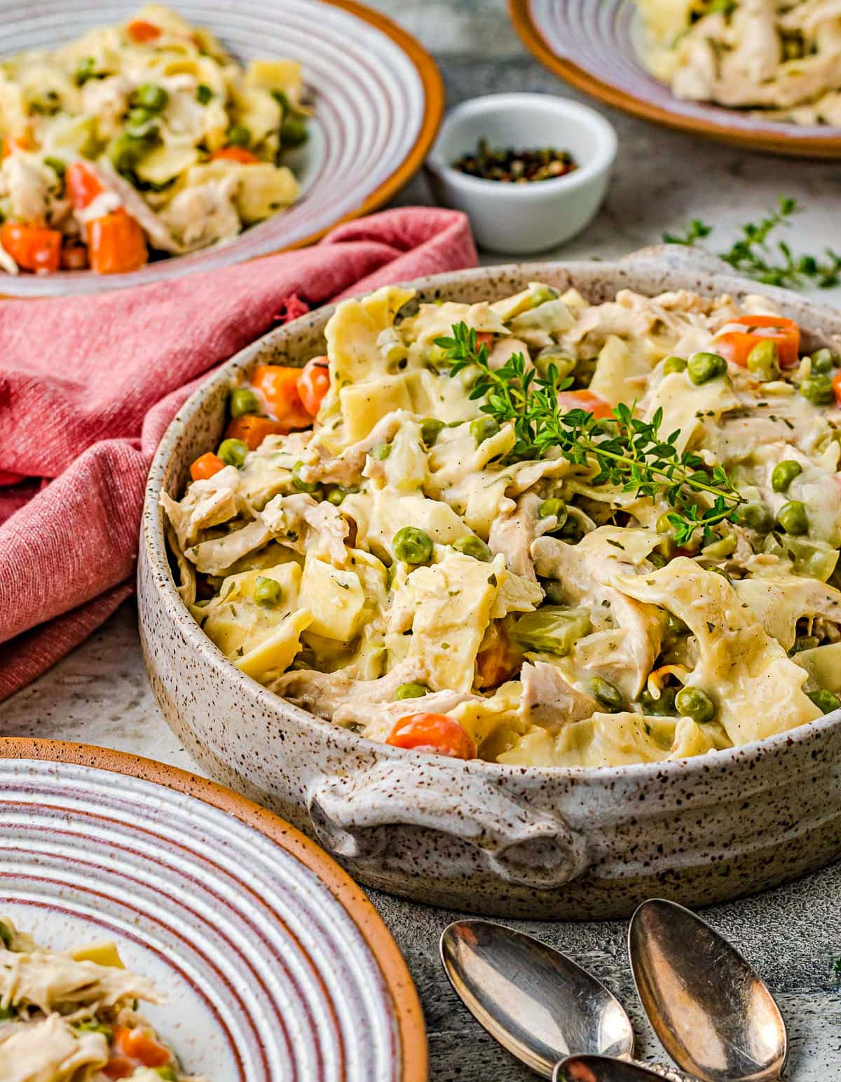 large pottery bowl filled with chicken noodles recipe topped with fresh thyme. Small dinner plates also have servings on them.