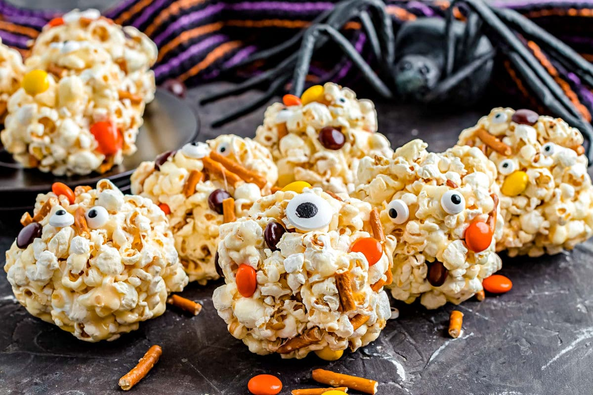 8 popcorn balls with candies and pretzel and candy eyes all ready for Halloween sitting on black surface.