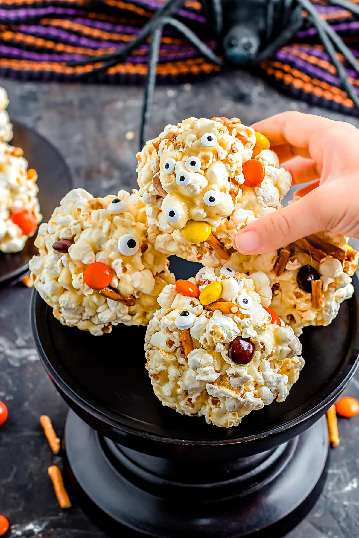hand picking up a halloween popcorn ball of a tall black cake stand.