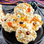 popcorn balls decorated for halloween with pretzels and candies sitting on black cake stand.