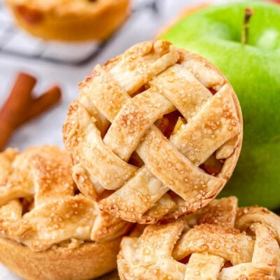 three mini apple pies resting near a green granny smith apple.