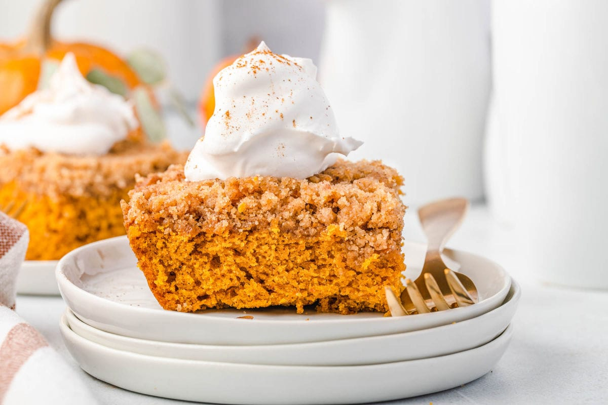 pumpkin coffee cake topped with whipped cream and a dusting of pumpkin pie spice sitting on 3 white stacked plates.