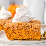 piece of pumpkin coffee cake sitting on stack of white plates topped with whipped cream
