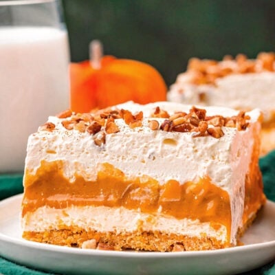 four layer pumpkin dessert sitting on white plate topped with pecans and pumpkin pie spice.