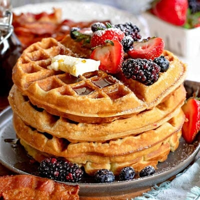 big stack of fluffy waffles topped with fresh berries butter and syrup.